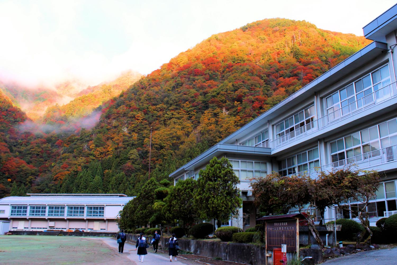 紅葉の中登校する生徒